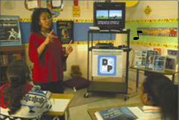A teacher stands next to a television displaying a captioned video.