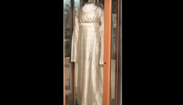 Vintage off-white, full-length dress in a glass case.