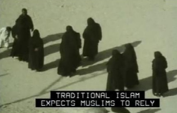Video capture of several people wearing dark robes and head coverings walking on sand. Captions are all caps white letters over a black background that read Traditional Islam expects Muslims to rely.