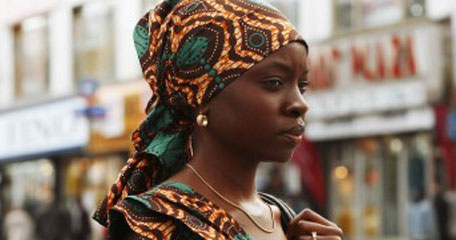 A young black woman wears a head scarf and walks through the city.
