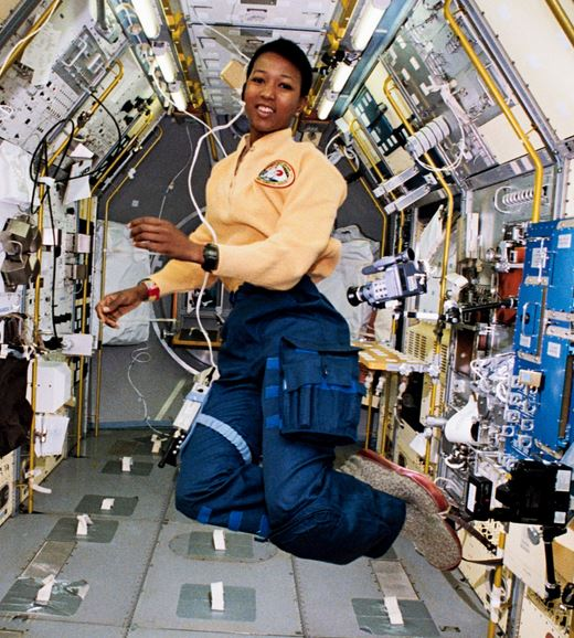 Mae Jemison floating inside a small room with numerous wires and electronics.