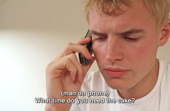 same teen from previous image speaking on cell phone. caption: (man on phone) When do you need the cake?
