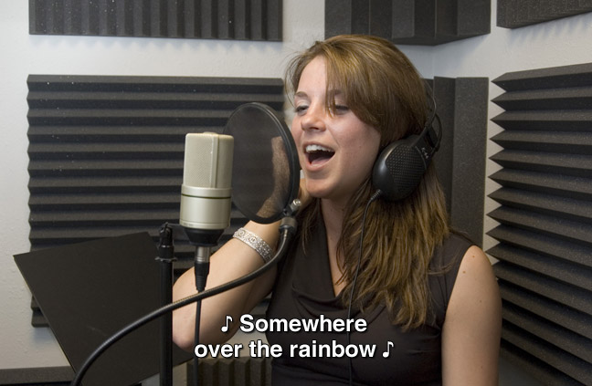 A woman sings in a small studio with a microphone. One musical note is one each end of the captioned sentence. caption: Somewhere over the rainbow.
