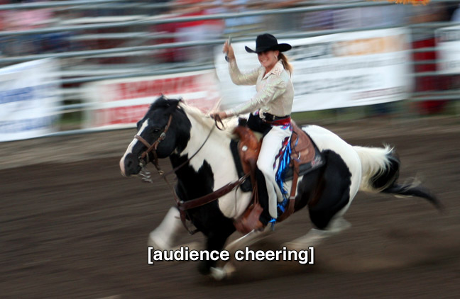 woman riding horse and twirling lasso at rodeo. caption: (audience cheering)