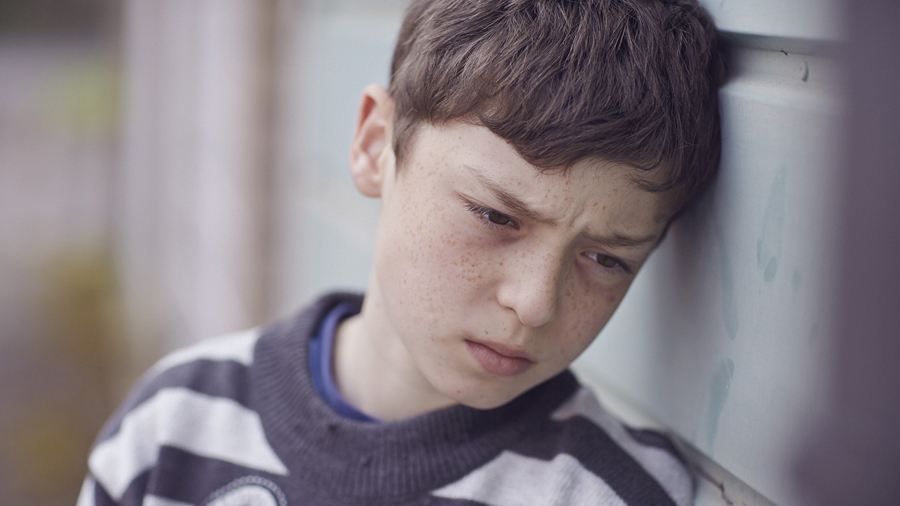 A young boy leans against a wall. His brow is knitted and he stares into the distance.
