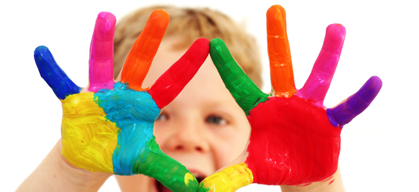 A young boy holds his hands up which are brightly painted with many colors.