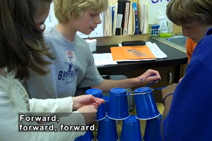 Kids in a classroom stack blue plastic cups.