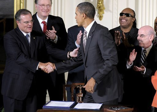 President Obama shakes hands with people at after signing communications and video accessibility act.