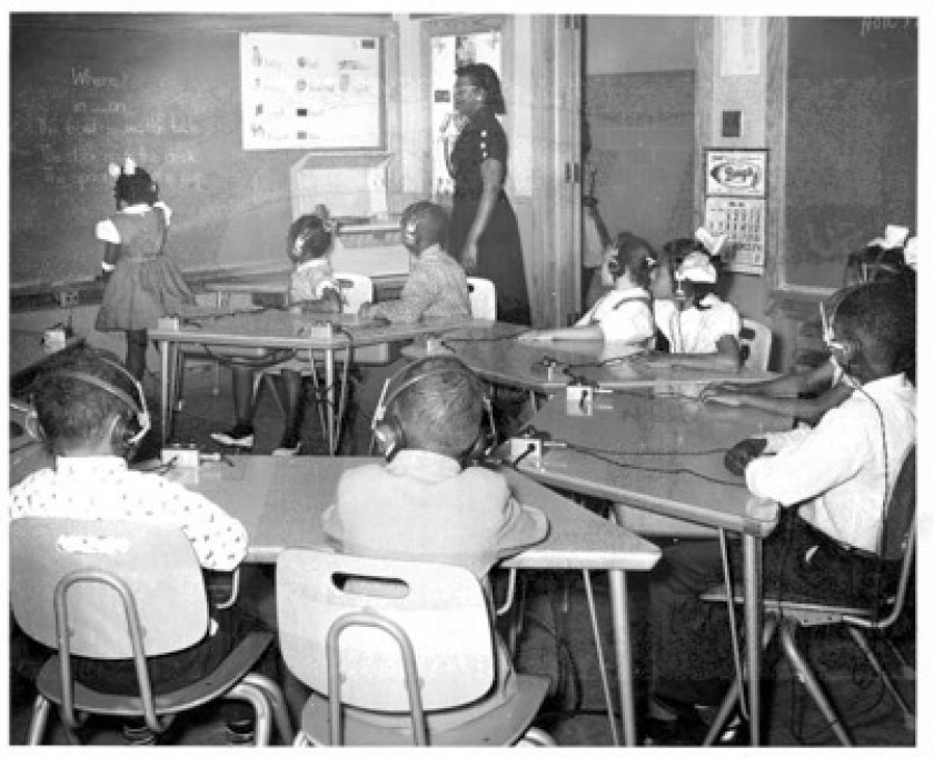 Vintage photo of Louisiana State School for the Colored Deaf and Blind classroom with several black students and a teacher.