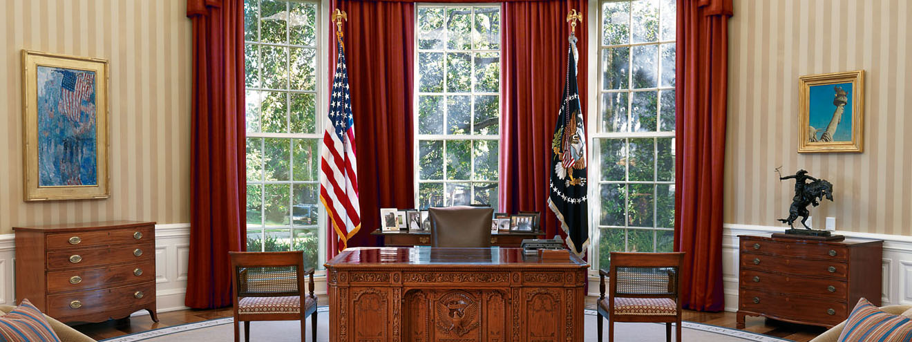 the oval office. a large carved wood desk with american flag behind it and three floor to ceiling windows with heavy drapes.