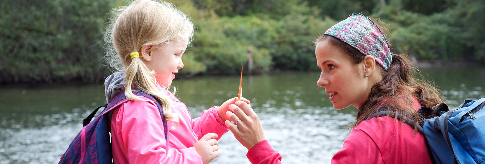 a mother and her young daughter are wearing jackets near a small body of water in a wooded area, looking at an orange leaf or feather held by the daughter.