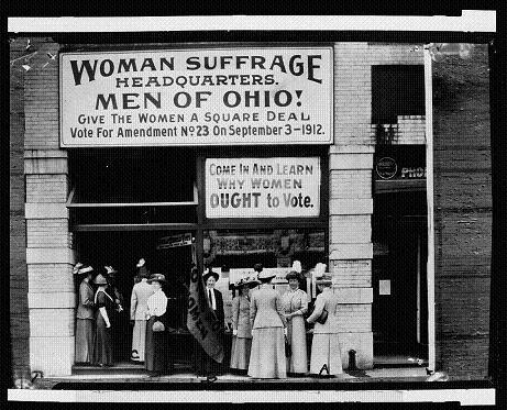 "Old Photo of building with large hand-painted sign saying ""Woman Suffrage Headquarters. Men of Ohio! Give the women a square deal. Vote for Amendment Number 23 on September 3, 1912. Come in and learn why women OUGHT to vote. Below signs, well-dressed women and men stand outside the entrance."