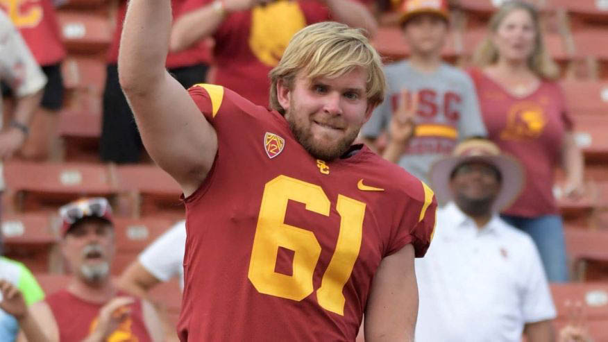 Jake Olson smiling and wearing a football uniform on the field.