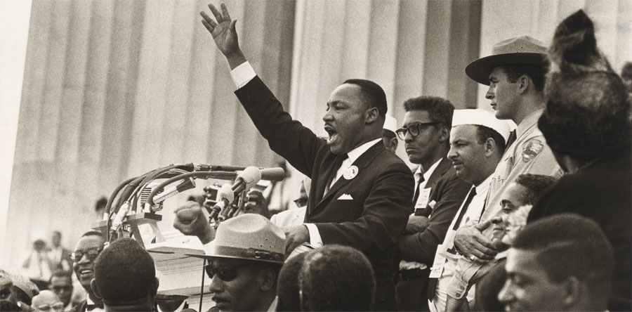 On the steps of the Lincoln Memorial, Martin Luther King, Jr. speaks passionately at a podium filled with microphones, his right arm raised, palm out. He is flanked by several people, including two park rangers.