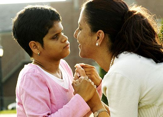 A young boy and his mother face each other, holding hands.