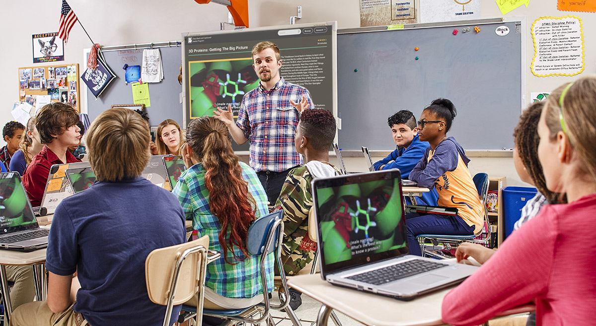 A teacher addresses his students in a classroom. A DCMP video pays on a white board and on students' laptops.