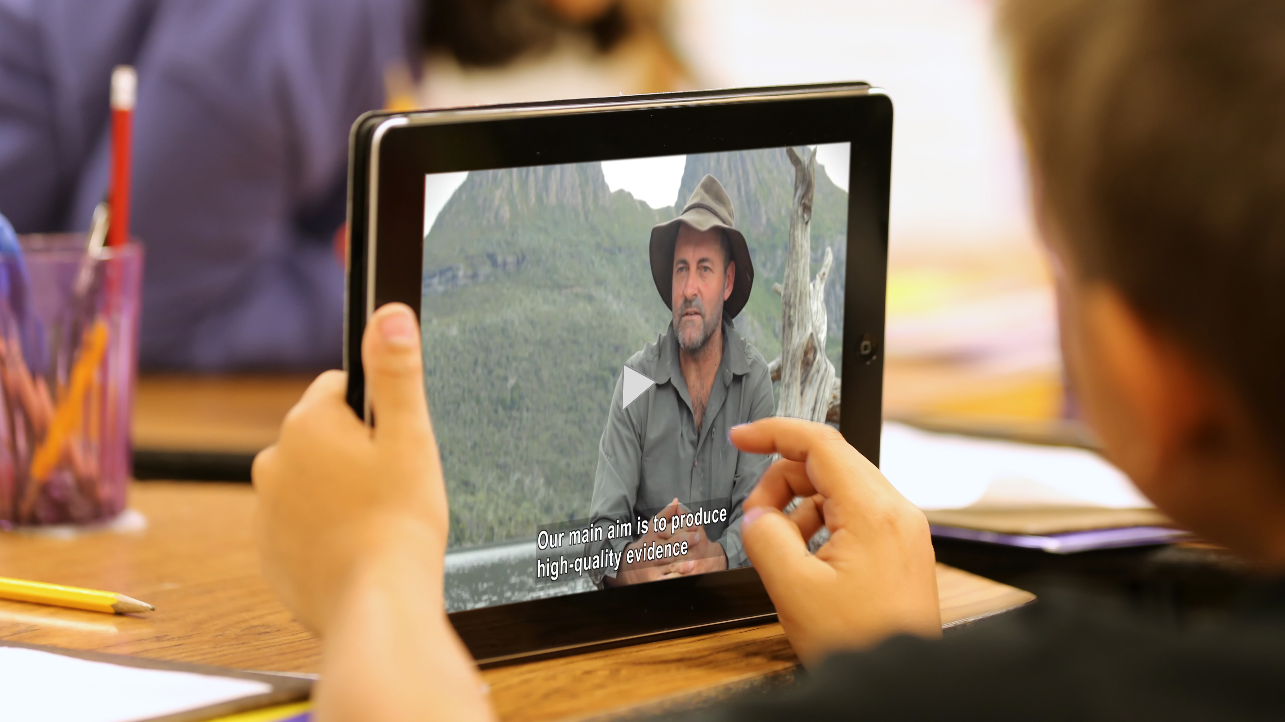 A student holds a computer tablet that is playing a captioned video.