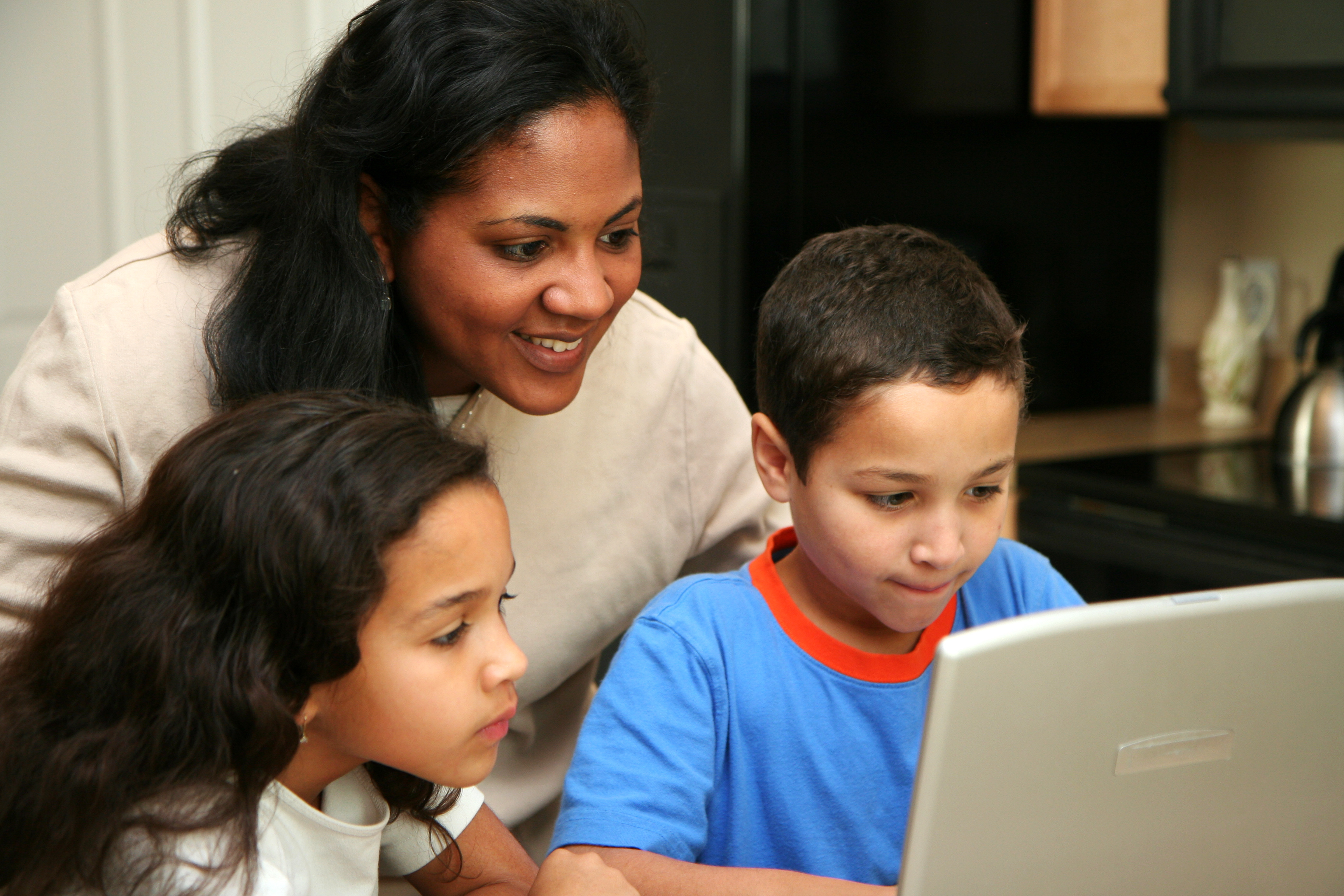A mother and two children at home smiling and looking at a laptop screen.