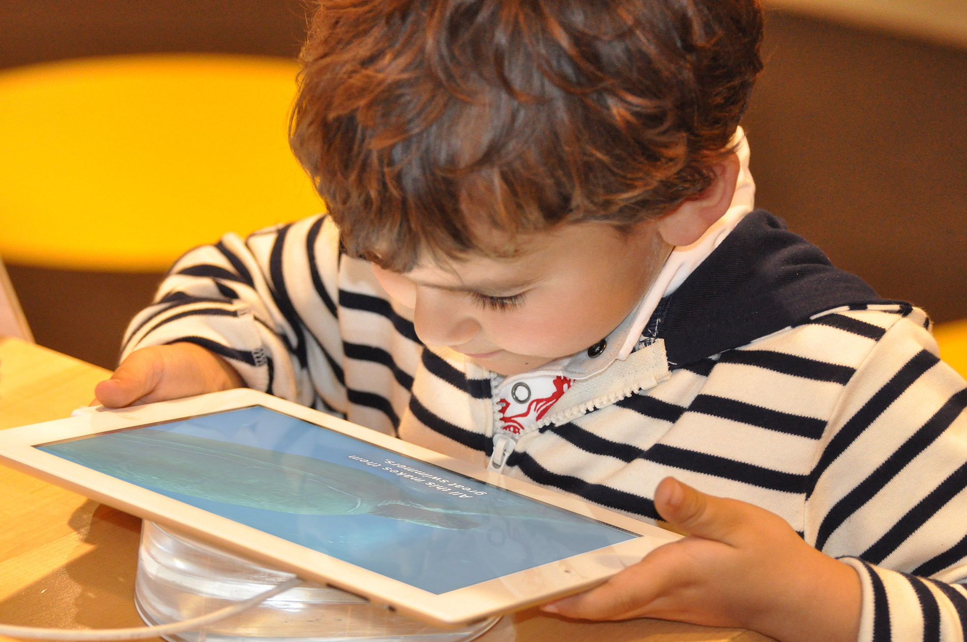 A young boy sits at a table, holding a tablet and watching a video on it.