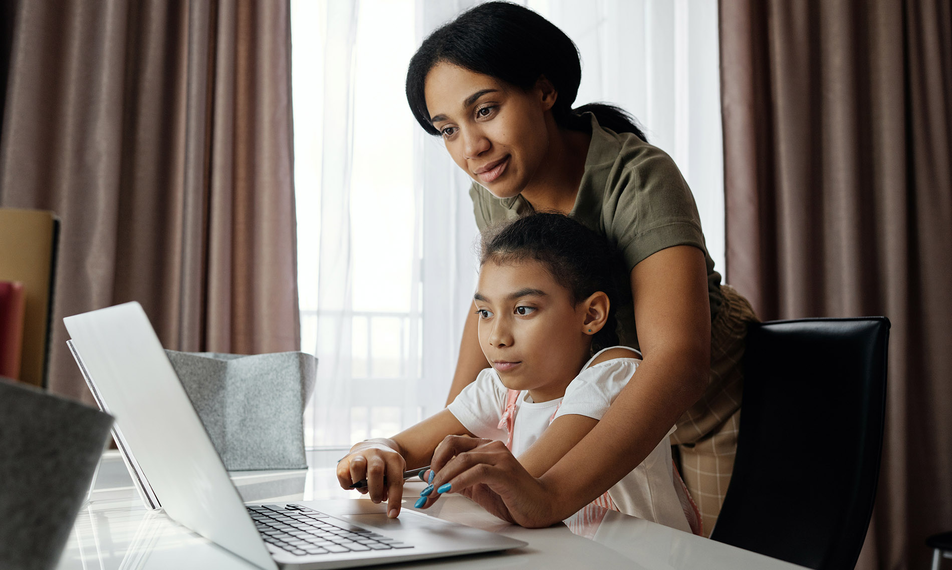 A mother stands behind her daughter who is seating at a desk at home. They are working on a laptop together.