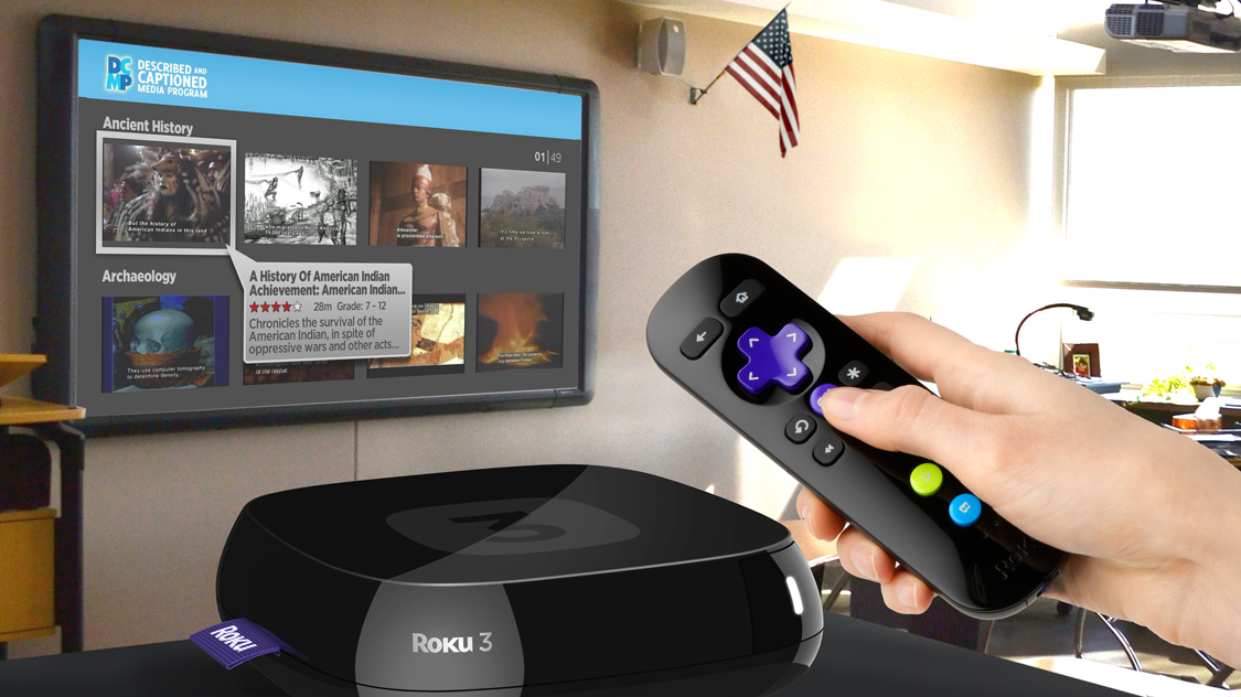 A wall mounted television in a classroom. A hand holds a remote control.