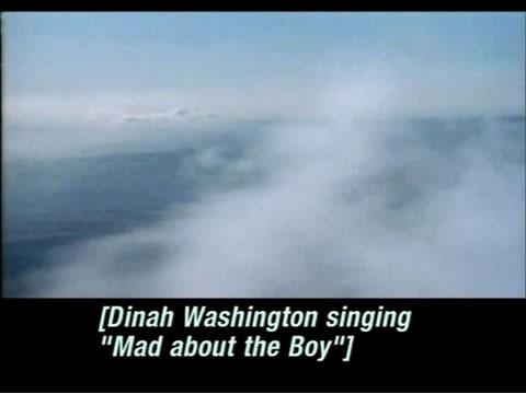 "Video still of clouds over the ocean. Caption reads: [Dinah Washington singing ""Mad about the Boy""]."
