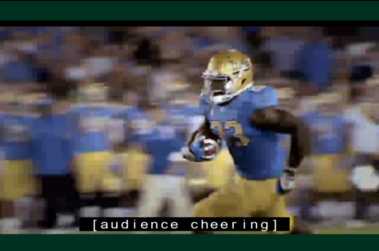 Video still of football game with man running with the ball. Caption reads: [audience cheering].