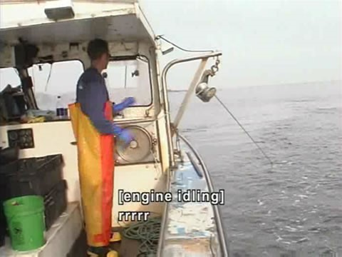 Video still of fisherman on a boat. Caption reads: [engine idling] rrrrr.