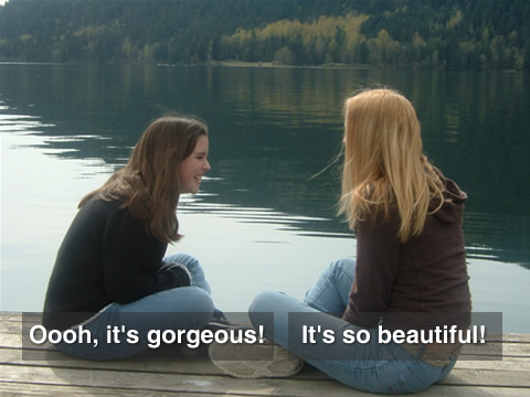 "Video still of two girls sitting on a lake dock. Captions read: ""Oooh, it's gorgeous!"" and ""It's so beautiful!""."